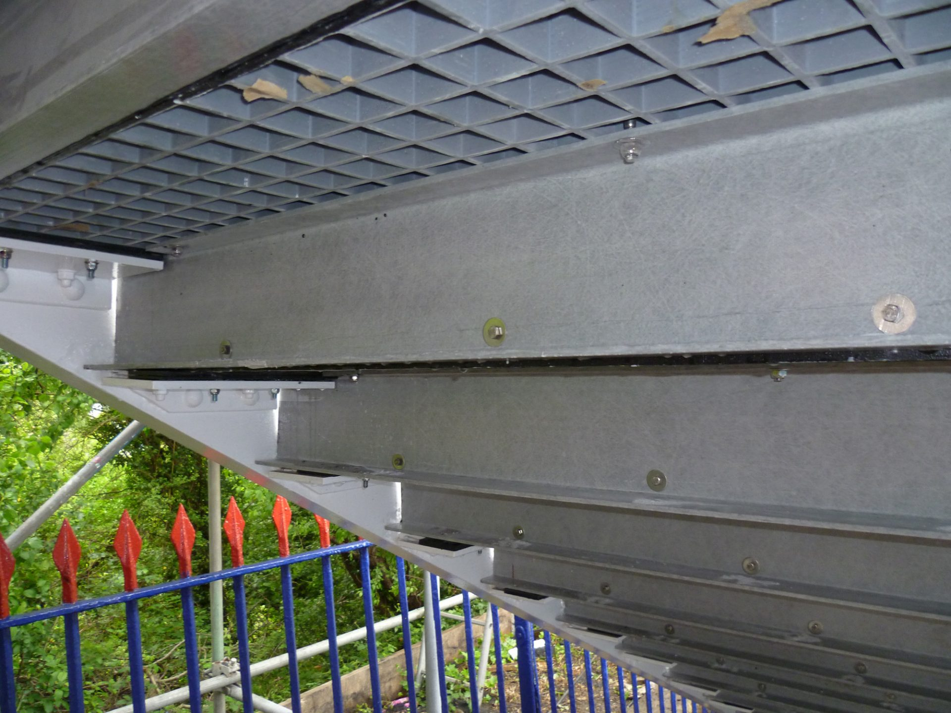 Underside of fibreglass load bearing stair treads replacing wood on historic footbridge